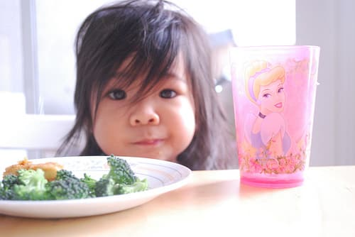kid with veggies and princess cup