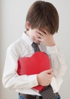 Young Boy Embarrassed Holding Heart Shaped Box