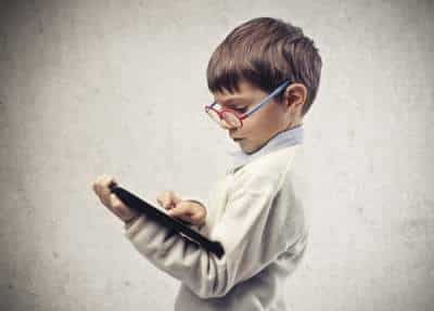 little boy with glasses and tablet