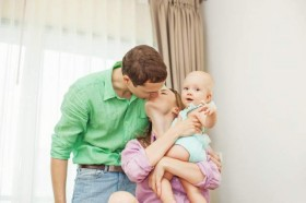 couple-kissing-with-baby