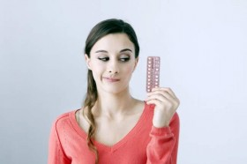 woman considering birth control pill