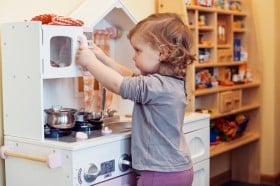 little girl playing with play kitchen