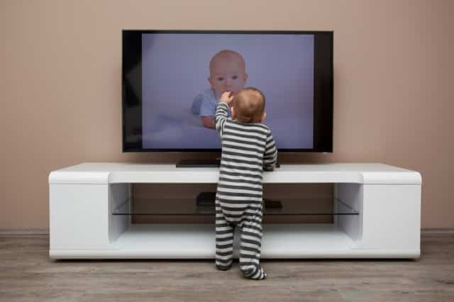 Toddler touching a baby on the television