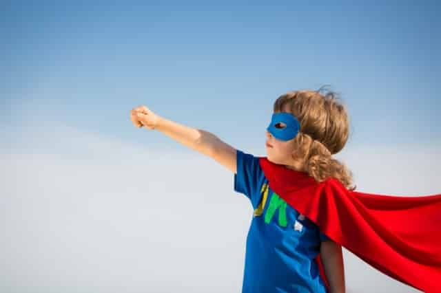 Young boy in red superhero cape and mask