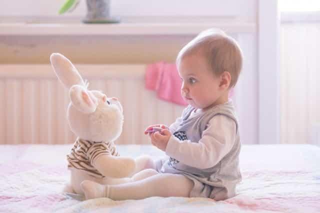 Baby girl playing with plush rabbit