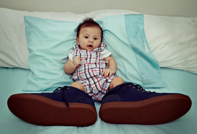 Asian Baby Wearing Big Shoes on The Bed
