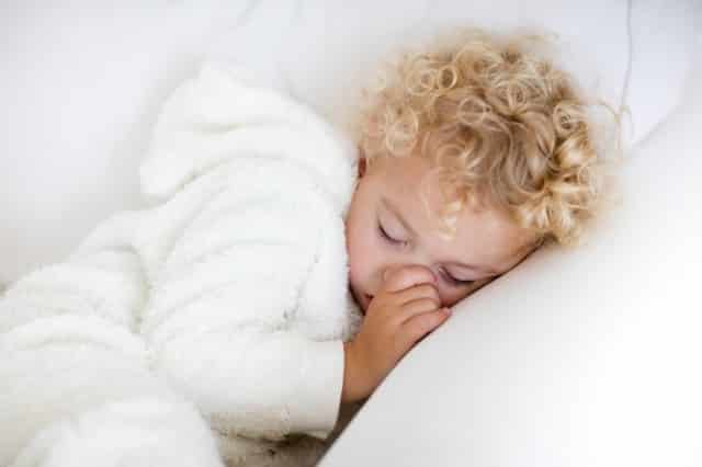 Cute blond curly little boy sleeping on white couch