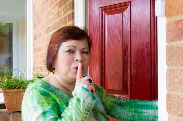 Woman spying near door of neighbour