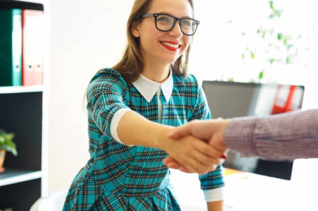 Modern business woman with arm extended to handshake
