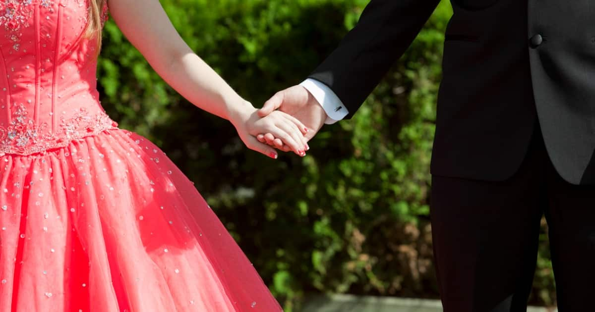male and female holding hands dressed for prom