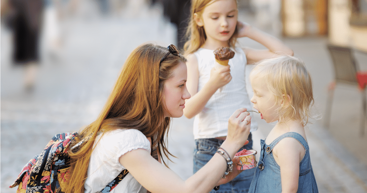 young babysitter with two young kids eating ice cream