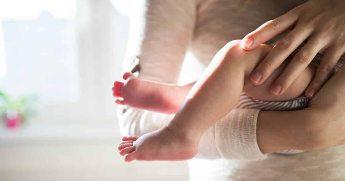 traumatic birth mom holding baby feet