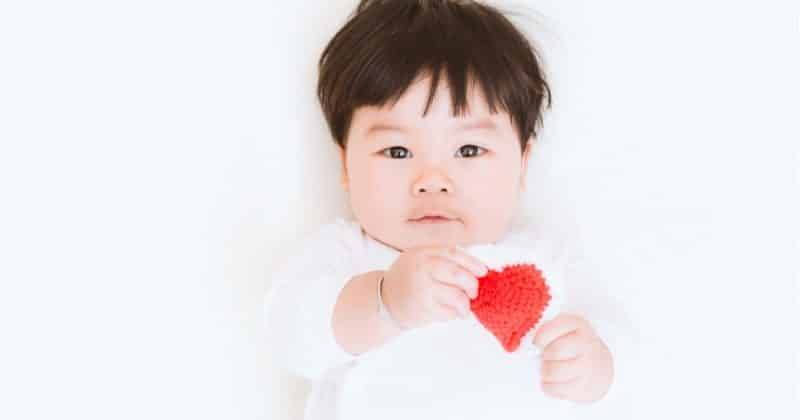 baby holding a heart