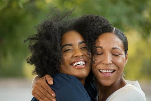 mom hugging grown daughter