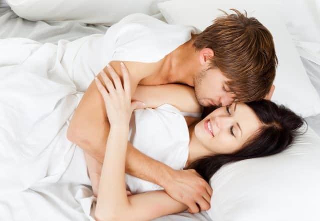 couple cuddling bed sleep